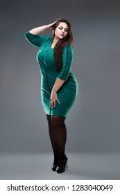 Plus size fashion model in blue dress, fat woman on gray studio background, overweight female body, full length portrait