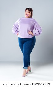 Plus size fashion model in casual clothes, fat woman on gray studio background, overweight female body