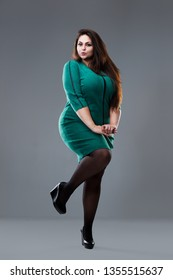 Plus size fashion model in green dress, fat woman on gray studio background, overweight female body, full length portrait