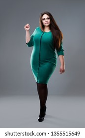 Plus size fashion model in green dress, fat woman on gray studio background, body positive concept, full length portrait