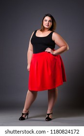 Plus size fashion model in red skirt, fat woman on gray studio background, overweight female body, full length portrait