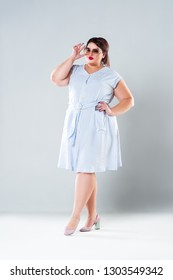 Plus size fashion model in striped dress, fat woman on gray background, overweight female body
