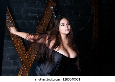 Plus size fashion model tied with chains to a wooden cross, fat woman in sexy clothes, love game and bdsm concept