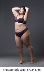 Plus size fashion model in underwear, young fat woman on gray studio background, overweight female body, full length portrait