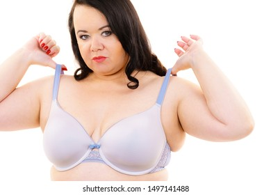 Plus size fat mature woman holding bra strap, on white. Female breast in lingerie. Bosom, brafitting and underwear concept.