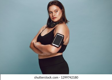 57580a787fa Plus size female model in sportswear with her arms crossed and looking  away. Confident fitness