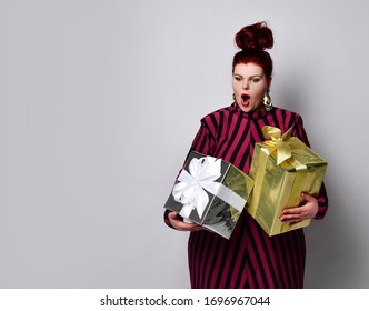 Plus size ginger model in black and purple striped dress and earrings. Holding golden and silver gift boxes, looking wild with joy, posing standing isolated on white. Close up, copy space