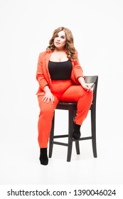 Plus size model with big breast and deep decollete, fat woman on white studio background in orange pantsuit, body positive concept