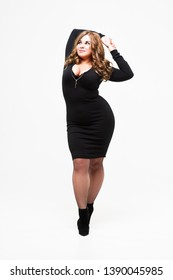 Plus size model in black dress, sexy fat woman on white background, body positive concept, full length portrait