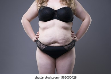 Plus size model in black lingerie, overweight female body, fat woman with stretch marks posing on gray background