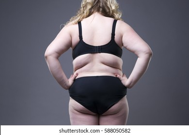 Plus size model in black lingerie, overweight female body, fat woman with cellulitis on buttocks posing on gray background