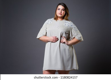 Plus size model in casual clothes, fat woman on gray studio background, overweight female body