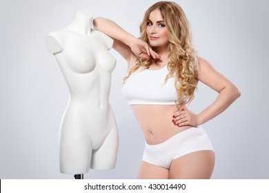 Plus size model and dummy female torso in studio
