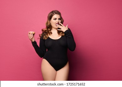 Plus size model girl in black bodysuit is holding sweet donut in her hand and licking her fingers, isolated at pink background with copy space. Concept of xxxl fashion