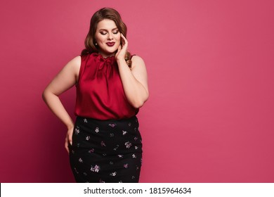 Plus size model girl with bright makeup and with stylish hairstyle in a red blouse and skirt isolated on the pink background