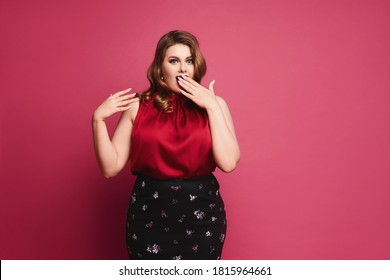 Plus size model girl with bright makeup in a red blouse and skirt isolated on the pink background.