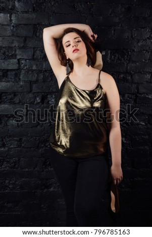 cf43a2f32 plus size model in a gold blouse and black jeans on a brick wall loft  background