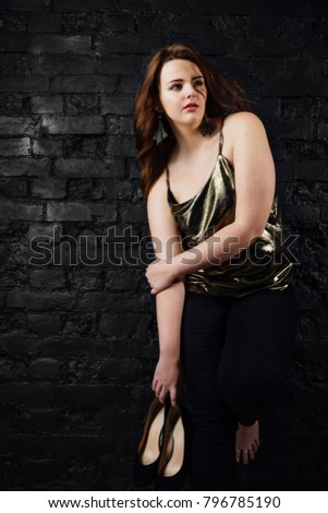 f879a83a7f78d plus size model in a gold blouse and black jeans on a brick wall loft  background