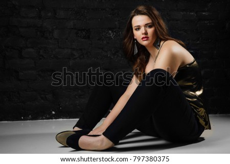 939755163 plus size model in a gold blouse and black jeans on a brick loft  background. Beautiful young brunette girl with long hair. Sexy