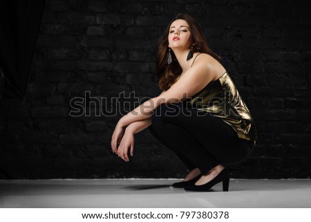 263613f44 plus size model in a gold blouse and black jeans on a brick loft background.