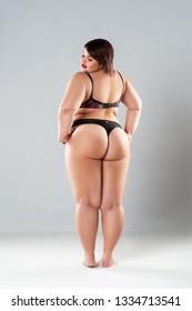 Plus size model in lingerie, fat sexy woman in underwear on gray studio background, body positive concept, full length portrait