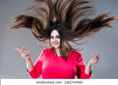 Plus size model with long hair blowing in the wind, brunette fat woman on gray studio background, body positive concept
