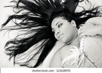 Plus size model posing like fashion models. The woman is posing is on the floor with her hair like Medusa, in a sexy manner.
