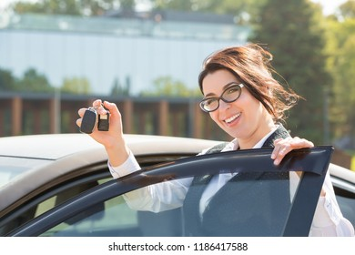 Plus size model standing near her own car and shows the keys. Buying or renting a car in the showroom