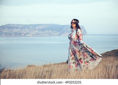 Plus size model wearing floral maxi dress posing in field. Young and fashionable overweight woman walking on the shore.