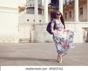 Plus size model wearing floral maxi dress posing on the city street. Young and fashionable overweight woman walking around town.