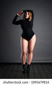 Plus size sexy model in black bodysuit, fat woman on gray studio background, overweight female body, full length portrait
