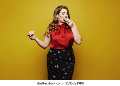 Plus size sexy model, fashionable blonde girl with bright makeup, in red satin blouse and black skirt, with donuts in her arm posing with closed eyes in studio at yellow background