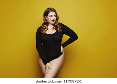 Plus size sexy model, fashionable blonde girl with bright makeup, in black bodysuit, with stylish hairstyle, smiling and posing at yellow background in studio