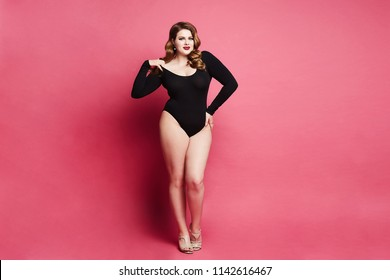 Plus size sexy model girl, fashionable blonde in black bodysuit, with bright makeup and with stylish hairstyle, smiling and posing at pink background in studio