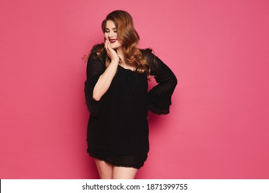 Plus size sexy model girl with bright makeup, fashionable blonde in black short dress posing at the pink background in studio