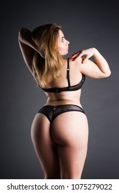 Plus size sexy model in lingerie, fat woman on gray studio background, overweight female body, full length portrait