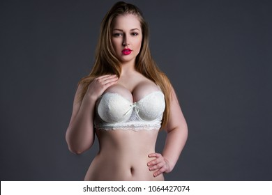 Plus size sexy model in white bra, fat woman with big natural breast on gray studio background, overweight female body, blonde hair and make-up