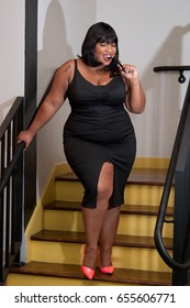 Plus size woman in a black dress coming down the stairs