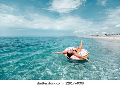 Plus size woman chilling on lilo in the sea water. Girl relaxing on inflatable ring on the beach. Summer vacations, idyllic scene.