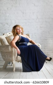 Plus size woman, curvy model, voluptuous silhouette and body, curvy hips. Plump girl, voluptuous, hourglass figure. Girl in blue evening dress.Portrait of a woman sitting in a chair in full growth