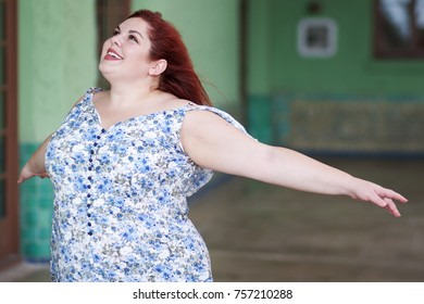 Plus size woman enjoying outside with her arms out flying