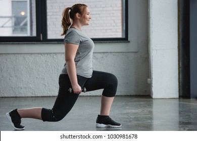 Plus size woman performing lunges with dumbbell in gym