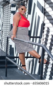 Plus size woman playing on a railing in a red bikini top and black and white skirt