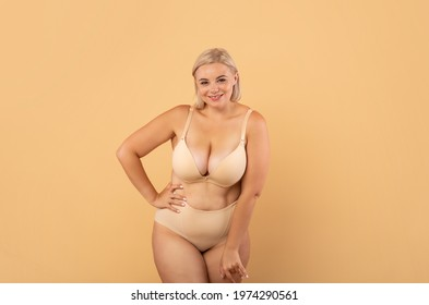Plus Size Woman. Portrait Of Beautiful Curvy Body Positive Lady Posing In Underwear, Attractive Young Oversized Female In Lingerie Standing Over Beige Studio Background, Smiling At Camera, Copy Space