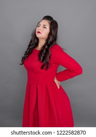 Plus size woman in red dress with pain in her back on gray background