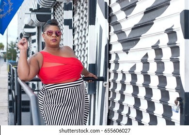 Plus size woman in a red top and black and white skirt
