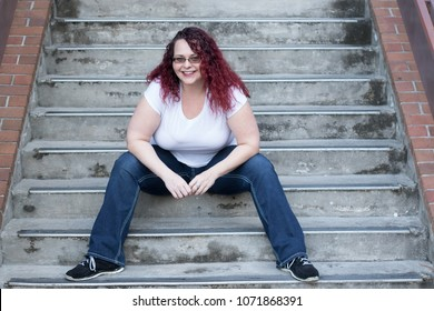 Plus size woman sitting on stairs