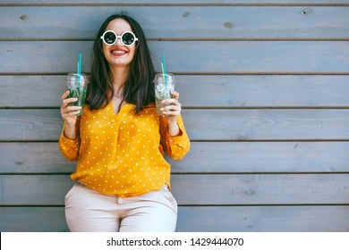 Plus size woman wearing yellow shirt and white hipster glasses smiling and drinking take away vegetable cocktail with ice in plastic cup with straw standing against cafe wall on city street.