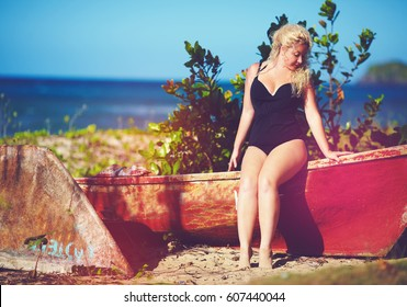 plus size young woman sitting on the boat on sunny beach