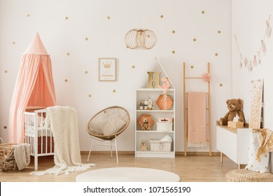 Plush bear on white cupboard in scandi child's bedroom interior with crib under canopy